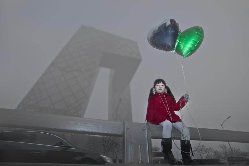 Wu Di in 2013 took a picture of a six-year-old holding up green balloons posing at various Beijing landmarks, such as the CCTV Tower case in point. Copyright@Wu Di,2019. All rights reserved.