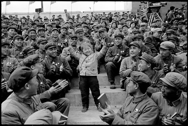 Li Zhensheng heard singing followed by a burst of applause. Following the sounds led the photojournalist to a young girl with unusually fair hair tied in ponytails, dancing with her arms upraised and surrounded by smiling, clapping soldiers. Credits: Li Zhensheng | SIPF