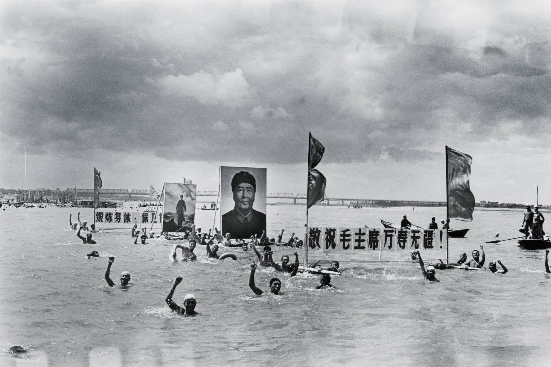 Swimmers praised Mao while floating along the Songhua River. Mao figured into many of Mr. Li's photographs — not in person but in portraits, busts and badges.Credit...Li Zhensheng Contact Press Images