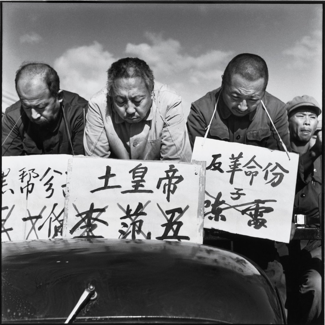 Three men are paraded through the streets of Harbin on Sept. 12, 1966, with their names and the crimes they are charged with from left, black gang element, local despot, counterrevolutionary displayed on placards. Credits: Li Zhensheng | SIPF
